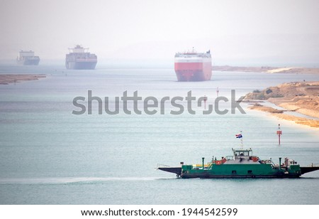 Suez Canal zone. Ship convoy in the distant desert haze. A local ferry between the east and west bank in foreground. Foto stock ©