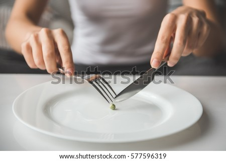 Suffering from anorexia. Cropped image of girl trying to put a pea on the fork Stock photo ©