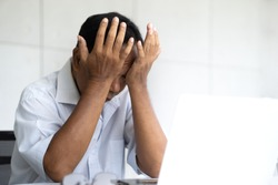 Suffering old aged asian man sitting in front of laptop feeling tired and depressed. Stress elderly male covering his face with both hands. He is an older hard working senior person.