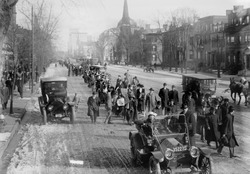 Suffrage hikers on way to Washington walking through Newark, New Jersey on Broad Street, February 12, 1913. The hike was organized and led by 'General' Rosalie Jones, leading behind the first car.