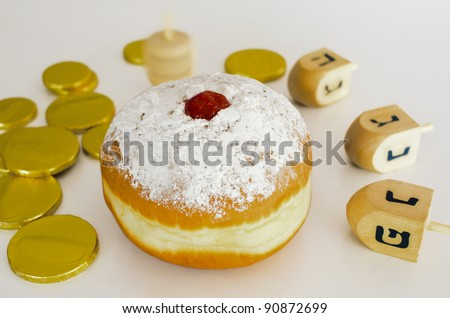 Sufganiya , Doughnut , with dreidel (spinning top), gelts (candy coins) for the Jewish holiday of Hanukkah.