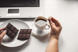 Sugar addiction, unhealthy lifestyle, weight gain, dietary, healthcare and medical concept. Woman pouring huge amount of sugar into coffee cup and eating sugary food, chocolate