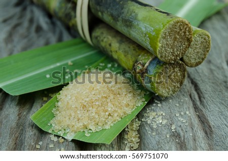 Sugar and Sugar cane on leaf and wooden background #569751070