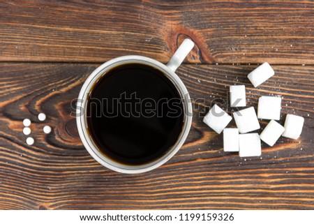 Sugar and sweetener on dark wooden background.