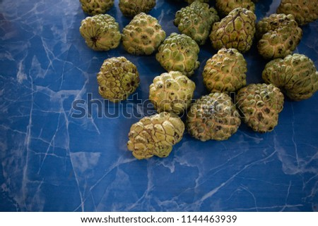 sugar apple or custard apple type of tropical fresh fruits , heap of organic nutrition diet fruit at asian market in Thailand . common useful vitamin for good foods .