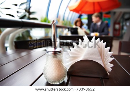 Sugar bowl and napkins in cafes and in the background a man and a woman at a table for lunch