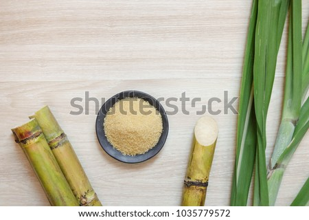 sugar cane and brown sugar on wooden table. #1035779572