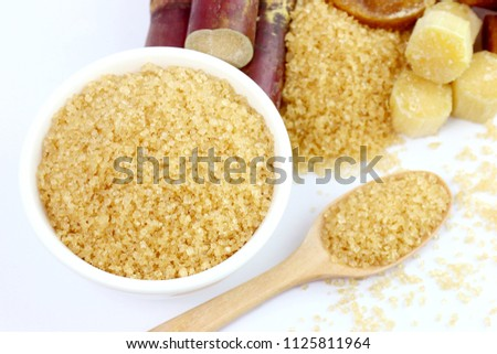 sugar cane and sugar, granulated sugar brown in a white cup, granulated sugar yellow on spoon wooden over white background