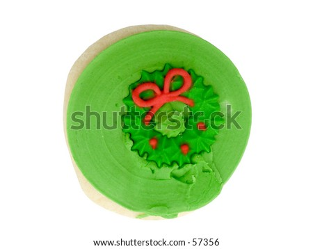 Sugar cookie with green icing and red Christmas wreath decoration on top.