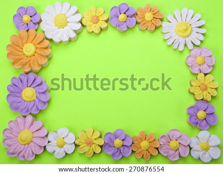 Sugar Cookies fancy home made flowers border isolated on a green background with room for your text in the center