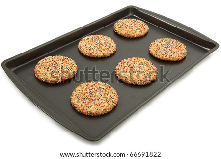Sugar Cookies With Colorful Sprinkles On Baking Sheet Over White Background