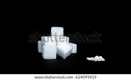 Sugar cubes and stevia pills next to each other in front of black background  #624099419