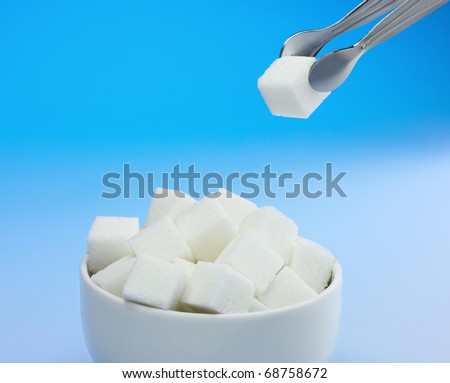 Sugar cubes in sugar bowl and sugar tongs