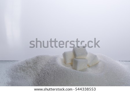 sugar cubes  on top of heaps of refined crystal sugar
