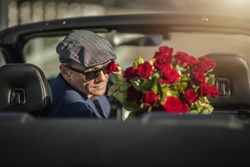 Sugar Daddy Eyes Seduction. Attractive Caucasian Men with Roses Awaiting His Girlfriend While Seating in a Convertible Car.