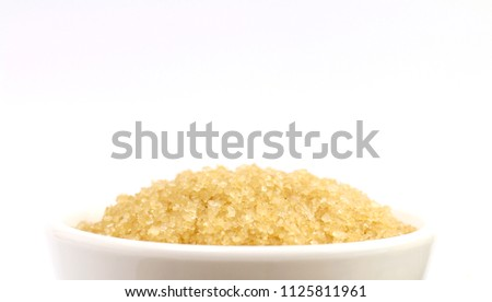 sugar, granulated sugar from sugar cane on a white cup (close up)