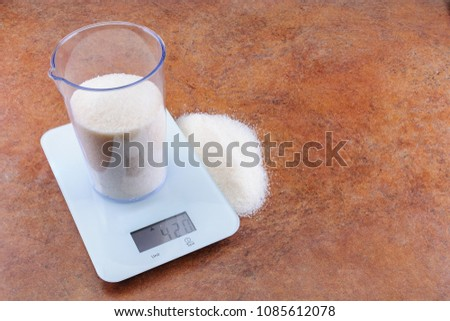 Sugar in a transparent measuring cup weighed on white electronic weighing The weight of 500 ml of the product is 420 grams. Part of the product is located on the desktop next to the scales.