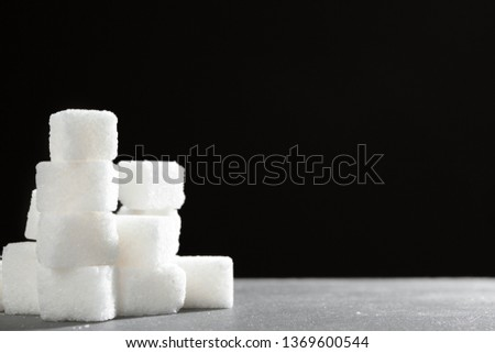 Sugar lumps piled up together against a black background #1369600544