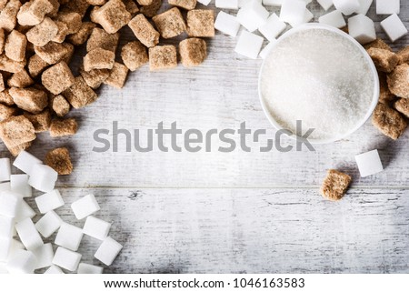 Sugar on white table in bowl. Sugar cubes brown and white from top view.