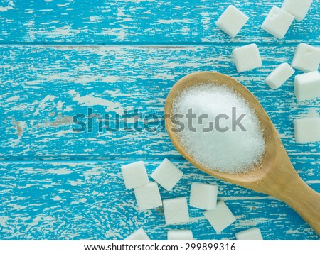 sugar on wooden spoon and cube sugar on wooden background