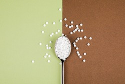 Sugar-replacing tablets with a spoon on a green-brown background.