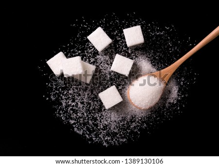 Sugar scattered from wooden spoons on a black background. Sugar wave. Sugar sand and sugar cubes poured from a wooden spoon.