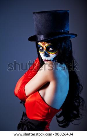 Sugar skull girl in tophat and red dress, studio shot