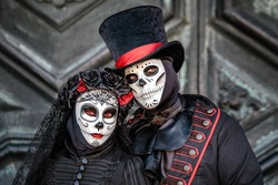 Sugar skull masked dressed as married couple  Day of the Dead style at Venice carnival, Italy.