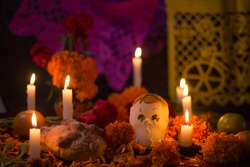 Sugar skull with candles, bread and flowers decoration for the day of the dead altar mexican tradition