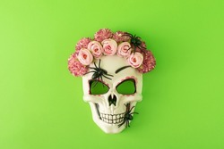 Sugar skull with colorful flowers and black spiders against green background. Minimal Halloween or Santa Muerte concept. Flat lay.
