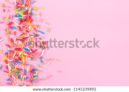 Sugar sprinkle dots hearts, decoration for cake and bakery, as a background. Isolated on pink