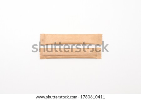 Sugar sticks on a white background. Sugar sticks without logo. Craft paper sugar bags. Sugar bags made of black paper. Mockup for applying a logo.