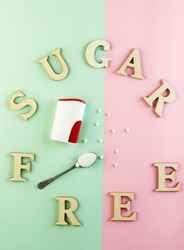 Sugar substitute pills and natural sweetener in powder on a green-pink background and sugar free inscription. Flat lay