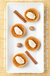 Sugar tart dessert top view. Mini sugar pies (or butter tarts) with a crisp pastry crust, a sweet filling and pumpkin spice whipped cream on top. A tasty dessert for fall holidays like halloween!