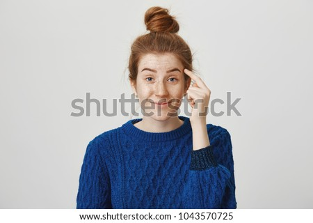 Suggest you sometimes use brains. Indoor shot of attractive redhead woman staring with contempt, holding index finger near temple, telling guy to think before acting stupidly, standing over gray wall
