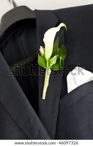 Suit jacket hanging on a hanger with a boutonniere in place.
