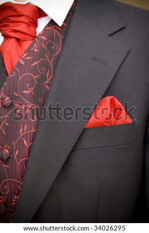 suit jacket of groom and red cravat ascot tie