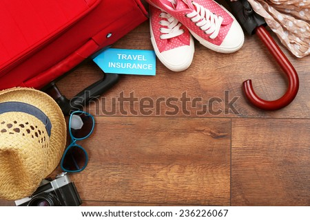 Suitcase and tourist stuff with inscription travel insurance on wooden background #236226067