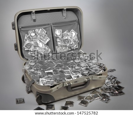 suitcase full of condfoms on grey background
