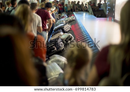 Suitcase on luggage conveyor belt at baggage claim at airport. Lines of people waiting for their baggage