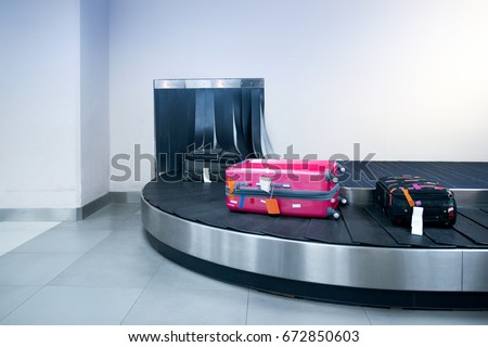 Suitcase or luggage is conveyed through the conveyor belt in arrivals lounge of airport terminal