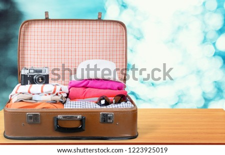 Suitcase with clothes and other travel accessories #1223925019