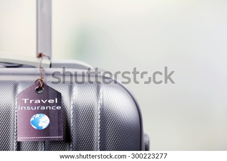 Suitcase with TRAVEL INSURANCE label on light blurred background #300223277