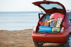 Suitcases and bags in trunk of car ready to depart for holidays. Moving boxes and suitcases in trunk of car, outdoors. trip, travel, sea. car on the beach with sea on background