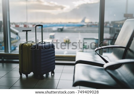 Suitcases in airport waiting area, winter holidays concept, two suitcases in airport departure lounge, airplane on the background