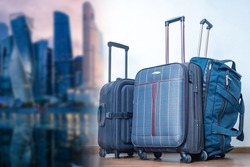 Suitcases on wheels on a blurred background of the city panorama. Journeys. Impressions of new places. Baggage rules. Carry-on baggage. Advertising of a travel company.
