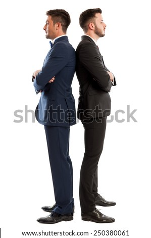 Suited and competitive business men standing back to back isolated on white background