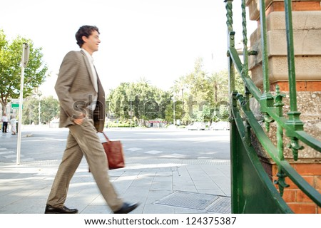 Suited businessman walking fast through the city on his way to work and carrying a briefcase, outdoors.