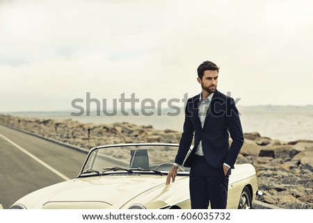 Suited dude with vintage car on road, looking away