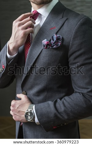 Suited man fixing his tie
